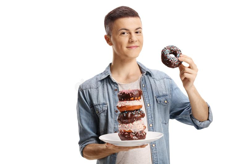 Male teenager holding a plate with a pile of chocolate donuts stock photos