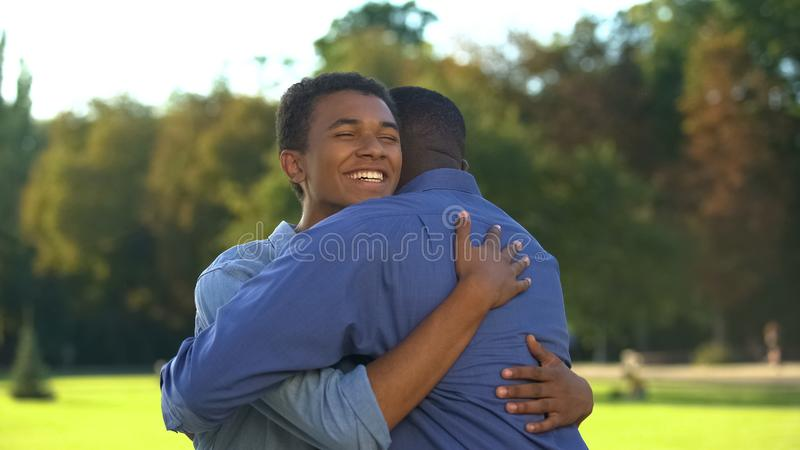 Male teenager hugging elder brother outdoors, family meeting happiness, love royalty free stock photography