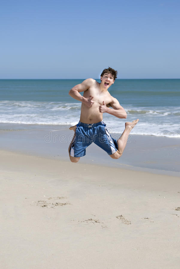 Male Teenager Jumping On Beach. Male teenager jumping on a beach, happy expression with thumbs up, ocean and sky background, vertical with copy space stock photos