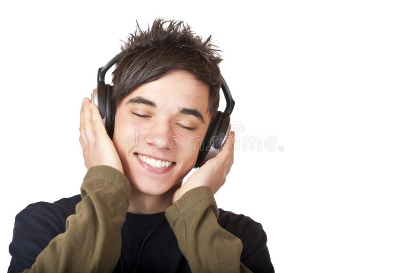Male Teenager listening to music via headphone royalty free stock photography