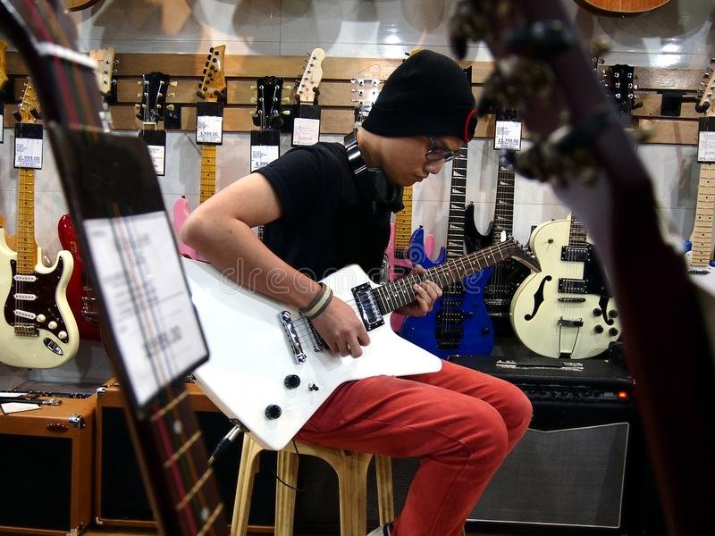 Male teenager playing guitar. At a guitar store royalty free stock image