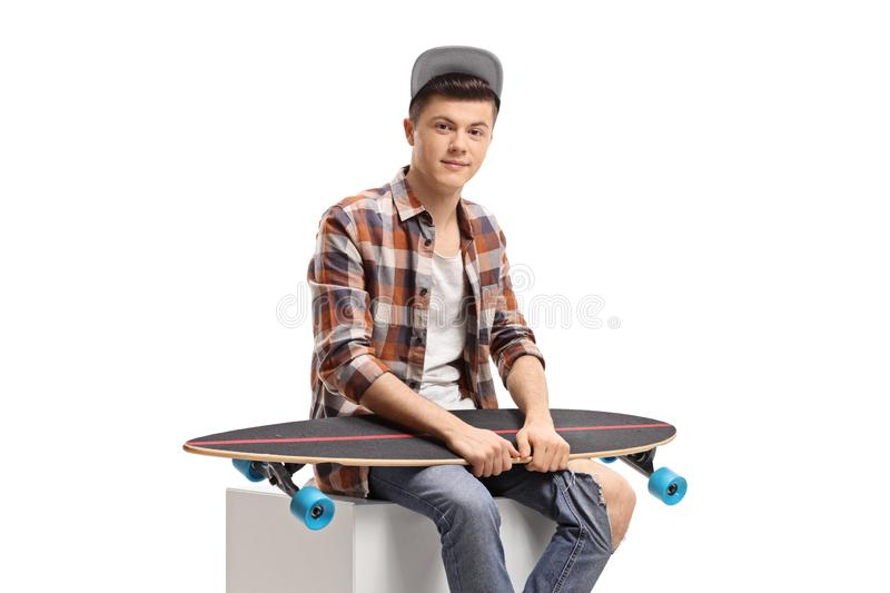 Male teenager sitting with a longboard stock photos