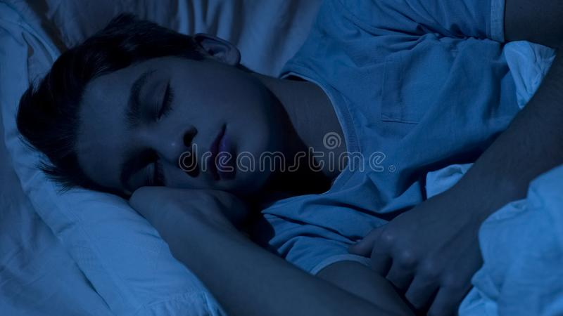 Male teenager sleeping healthy at night time, close-up of child face, relax royalty free stock photo