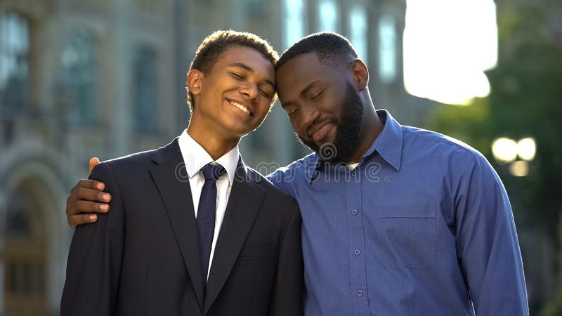 Male teenager in suit and happy father smiling, celebrating prom near university royalty free stock photo