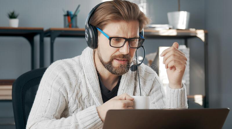 Male teleworking, headset on. Casual-dressed male with headset teleworking sitting in front of computer, isolation due to epidemic stock photos