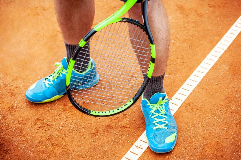 Male tennis player legs in tennis shoes standing on a clay court royalty free stock photography