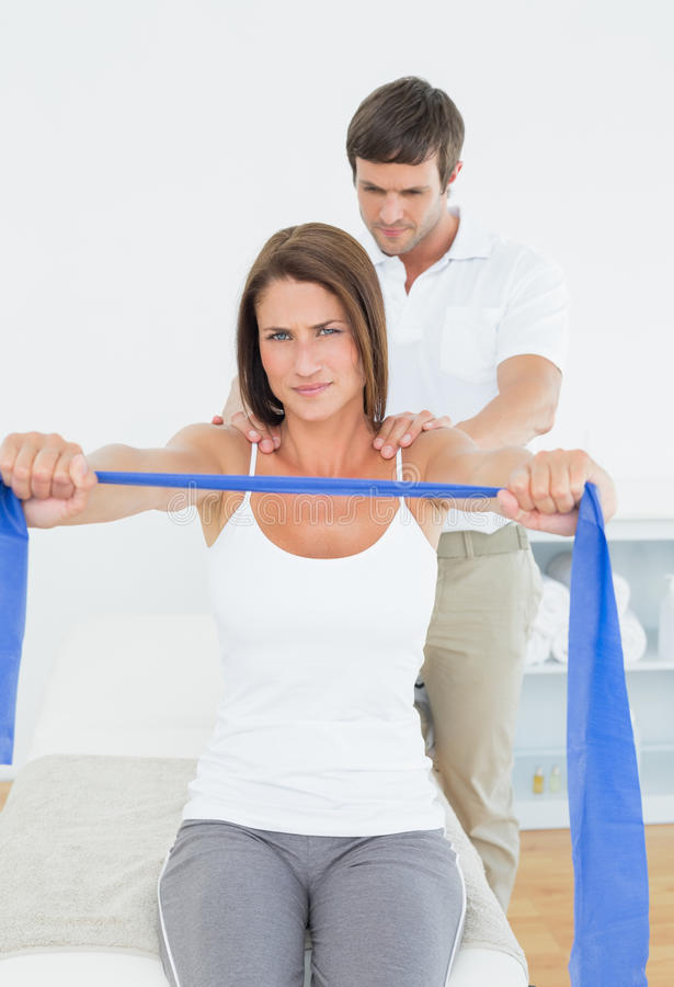 Male therapist assisting young woman with exercises stock images