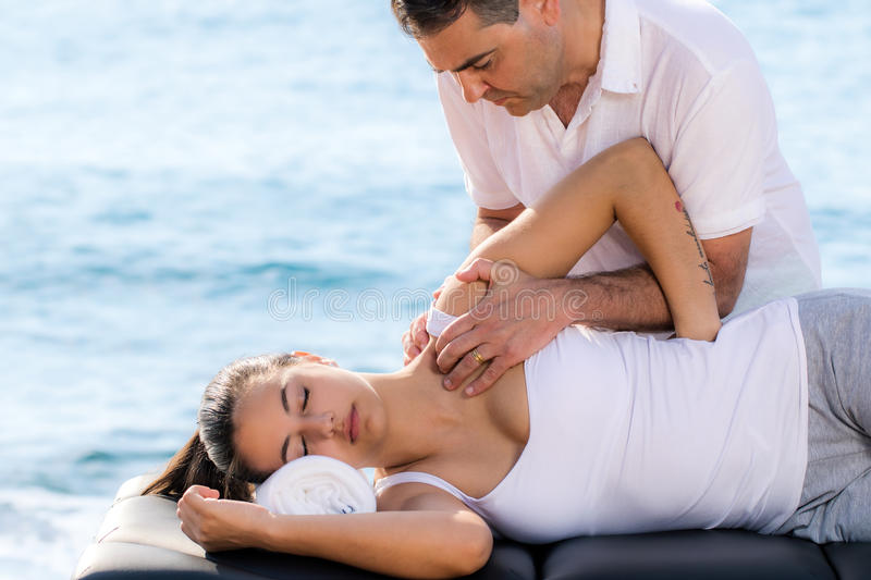 Male therapist doing shoulder treatment on woman outdoors. royalty free stock images