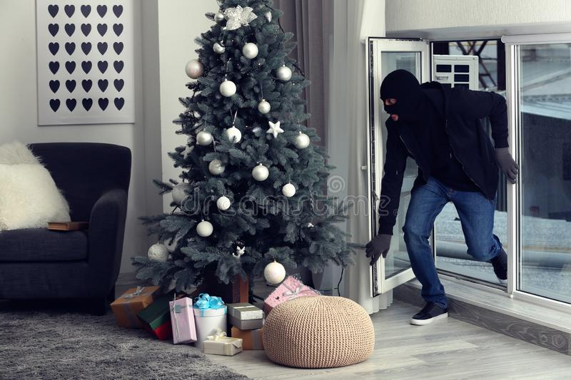 Male thief entering house through window stock photography