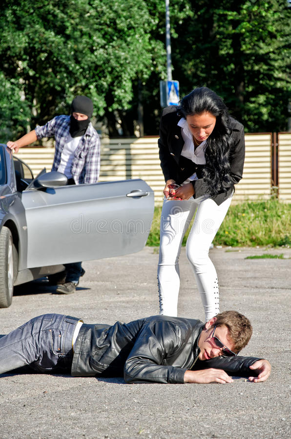 Male thief stealing a car. While his accomplice distracts female driver stock image