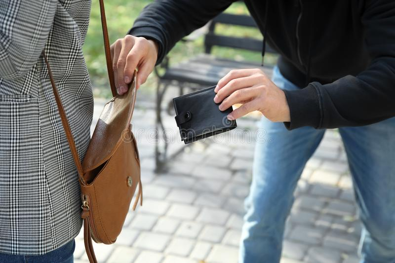 Male thief stealing wallet from young woman in park stock images