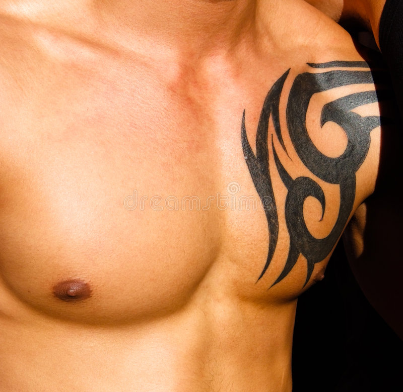 Male torso with tattoo. With a dark background royalty free stock photography