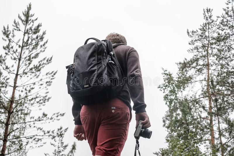A male tourist with a backpack and a camera in his hand is standing on the top of a hill, against the background of overcast skies. And pines. Close-up royalty free stock photos