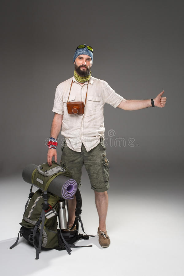 Male tourist with backpack hitchhiking on gray. Full length view of male tourist with backpack hitchhiking on gray background stock photography