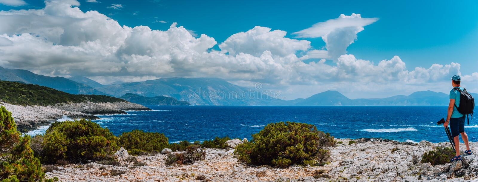 Male tourist with camera admiring breathtaking cloud scenery over the mountain range at the Mediterranean sea coast royalty free stock images