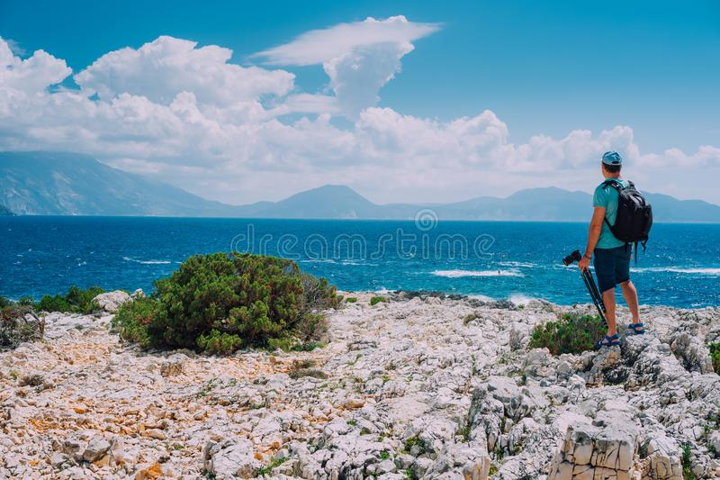 Male tourist with camera admiring breathtaking cloud scenery over the mountain range at the Mediterranean sea coast stock photos