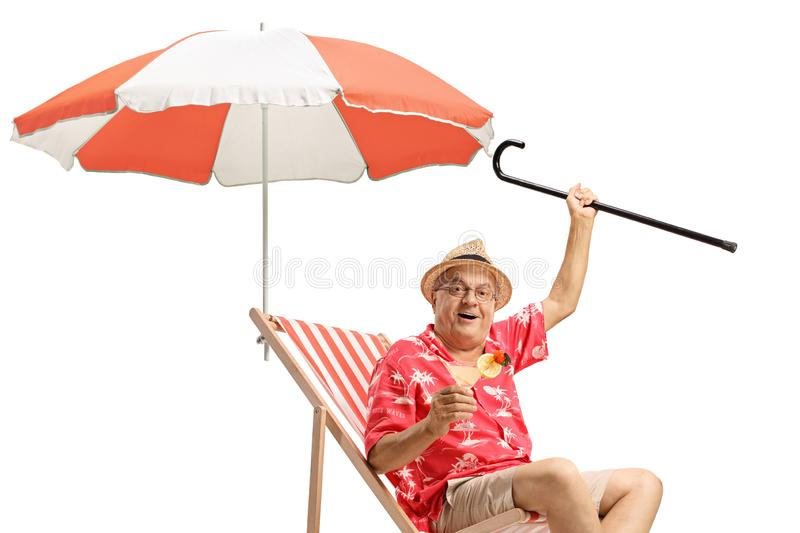 Male tourist with a cocktail and a cane sitting in a deck chair with an umbrella stock image