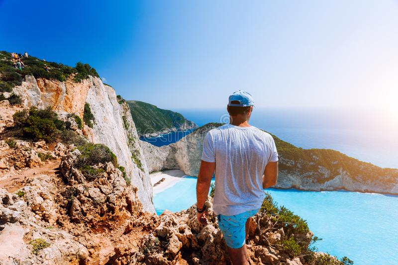 Male tourist enjoying spectacular view from the highs to Navagio beach on Zakynthos island stock photos