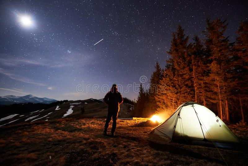 Male tourist have a rest in his camp near the forest at night under beautiful night sky full of stars and the moon stock photography