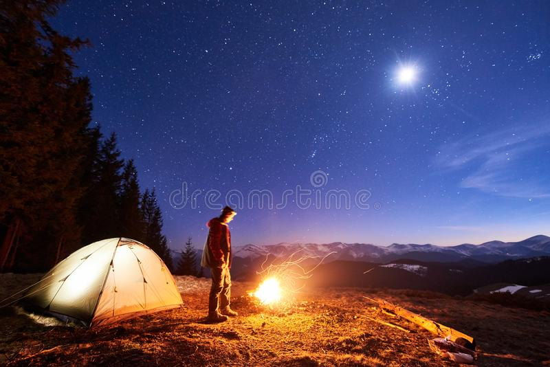 Male tourist have a rest in his camp at night, near campfire and tent under night sky full of stars and the moon. Male tourist have a rest in his camp at night royalty free stock photos