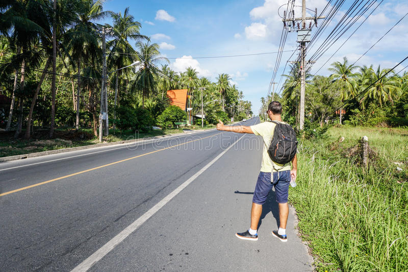 Male tourist hitchhiking on roadside by highway. On Samui island, Thailand royalty free stock images