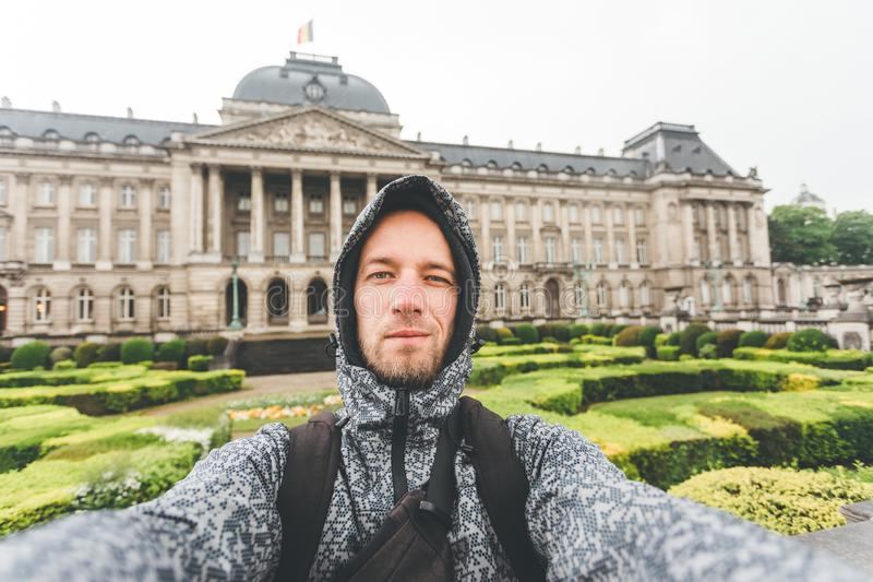 Male tourist takes selfie picture against the backdrop of the Royal Palace in Brussels, Belgium royalty free stock image