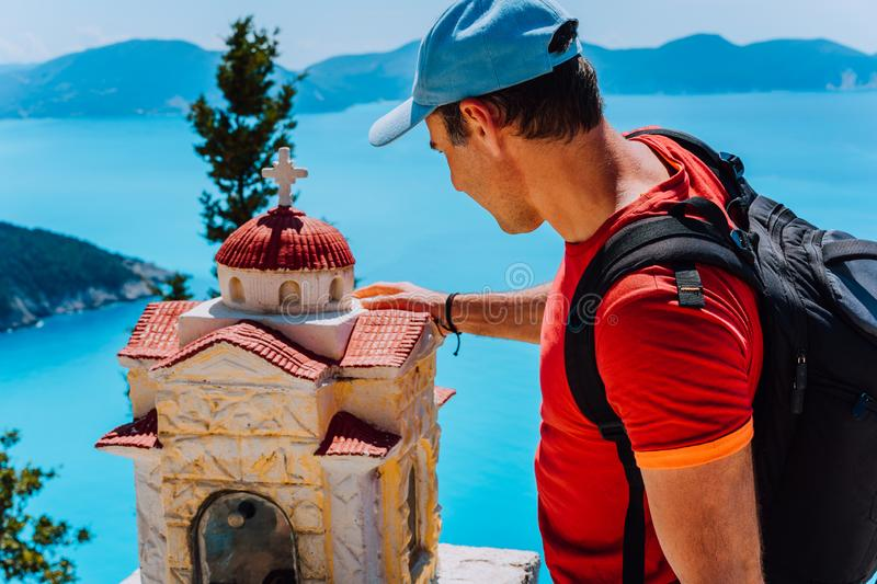 Male tourist touches thoughtful to small Hellenic shrine Proskinitari, Greece. Amazing sea view in the background stock image