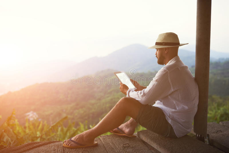 Male tourist is using touch pad, while is sitting against amazing jungle scenery. Young man traveler is holding digital tablet with empty screen background with royalty free stock photo
