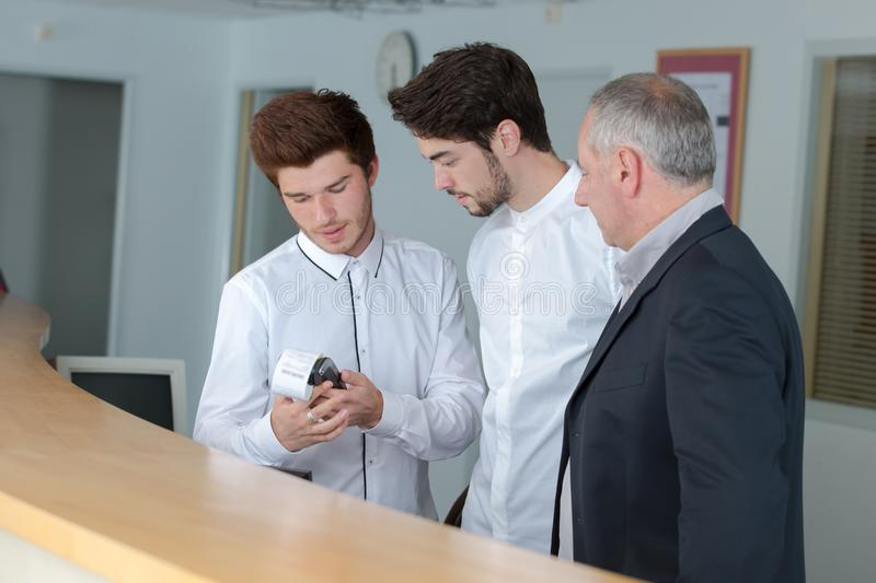 Male trainee receptionists in receptionist class. Receptionists stock images