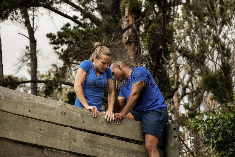 Male trainer assisting woman to climb a wooden wall royalty free stock photography
