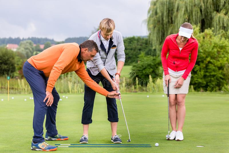 Male trainer teaching the couple to play golf royalty free stock photography