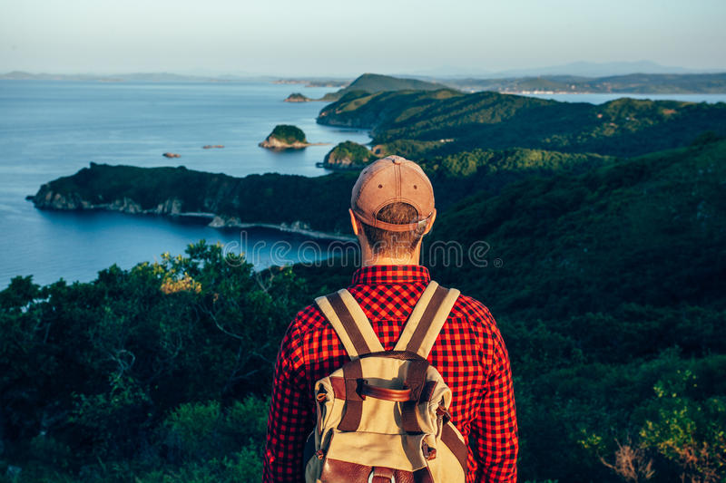 Male traveler from back on the sea coast stock photography