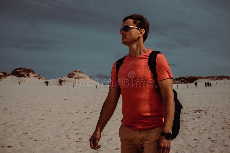 Male traveler with backpack explore polish sand dune near Gdansk. Caucasian adult man tourist alone travel to Poland. Adventure royalty free stock photos
