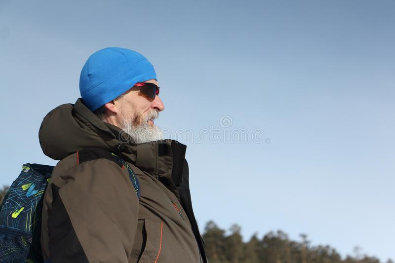 Male traveler with a beard in a blue hat and sunglasses against the blue sky stock photos