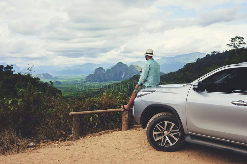 Male traveler is dreaming about something, while is sitting on a car hood against Amazon view. Young man wanderer is enjoying beautiful landscape during summer royalty free stock image