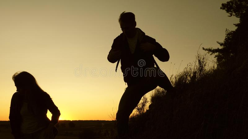 Male traveler and female traveler descend from the top of the hill. teamwork of business people. tourists descend from. Male traveler and female traveler descend royalty free stock images
