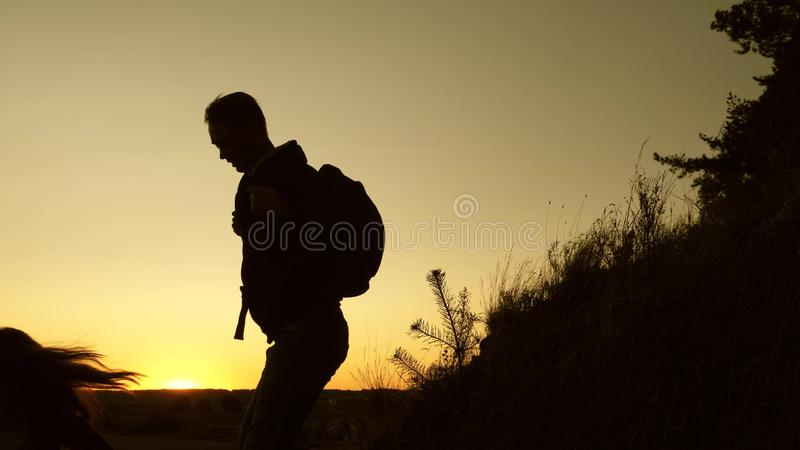 Male traveler and female traveler descend from the top of the hill. teamwork of business people. tourists descend from. Male traveler and female traveler descend stock photo