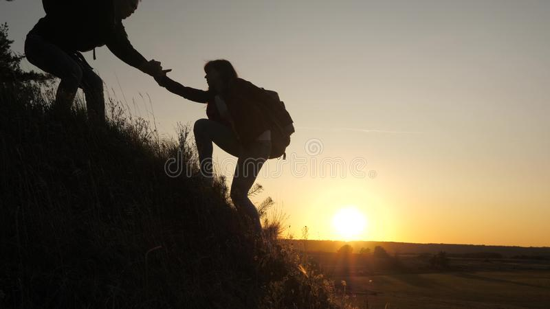 A male traveler holds out his hand to female traveler climbing a hilltop. Tourists climb the mountain in the sunset. A male traveler holds out his hand to a stock image