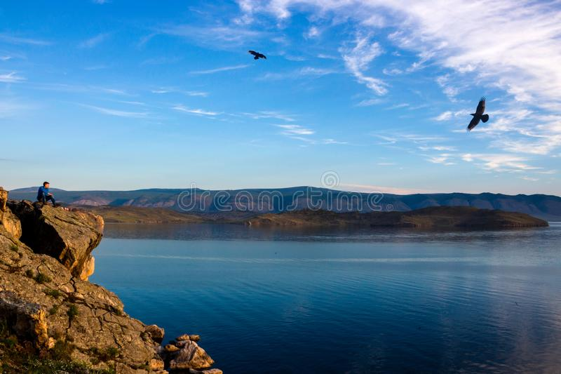 Man sitting on the edge of a cliff above Lake Baikal. Male traveler sits on the edge of a rock above Lake Baikal at dawn and admires the flight of a pair of royalty free stock photos