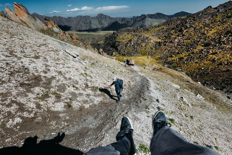 Male Traveler Sits On Top Mountain And Enjoys Mountain View In Summer. Group Of Tourists Climbs Uphill. Point Of View Shot royalty free stock images