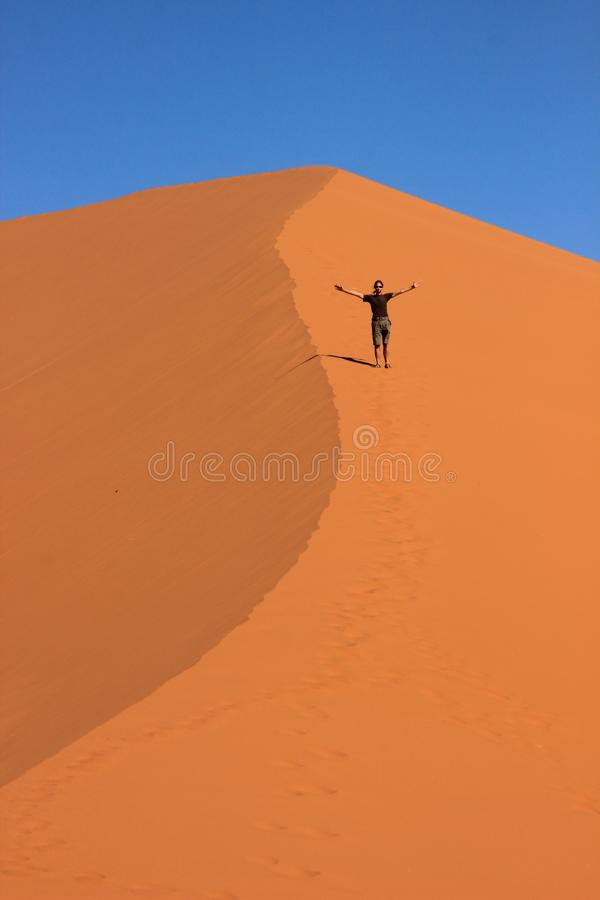 A male traveler in sportswear is standing on the orange sand of a dune in Sosusfle National Park stock photos