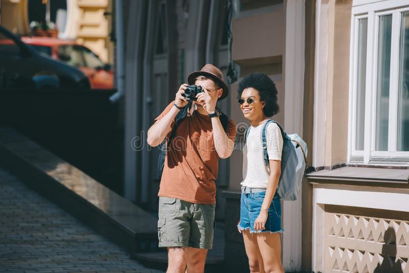 Male traveler taking picture on camera and african american girlfriend. Standing near royalty free stock images
