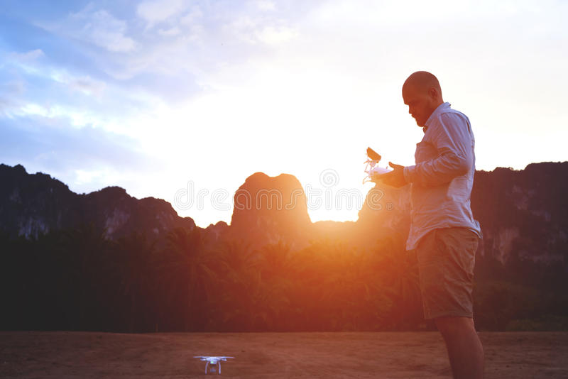 Male traveler is using quadcopter during his unforgettable trip in Thailand. Silhouette of a young man is holding remote control of a drone, while is standing royalty free stock photography