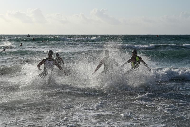 Male triathletes enter the surf at the start of the 2019 South Beach Triathlon. stock photography
