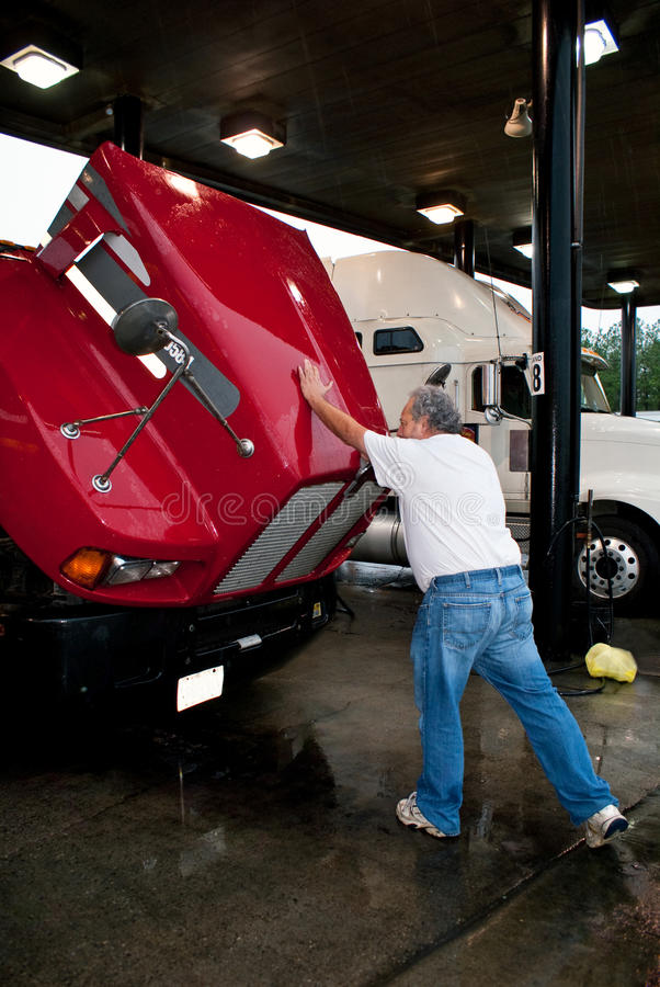 Male truck driver closing hood of 18-wheeler. Red tractor at truck stop royalty free stock photos