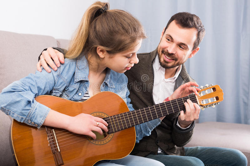 Male tutor assisting teenage pupil in learning how to play guitar stock photography