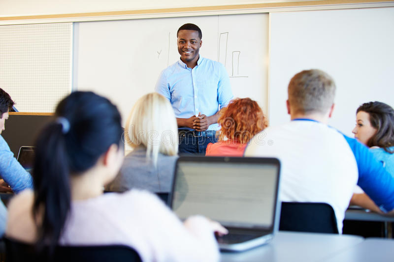 Male Tutor Teaching University Students In Classroom royalty free stock images