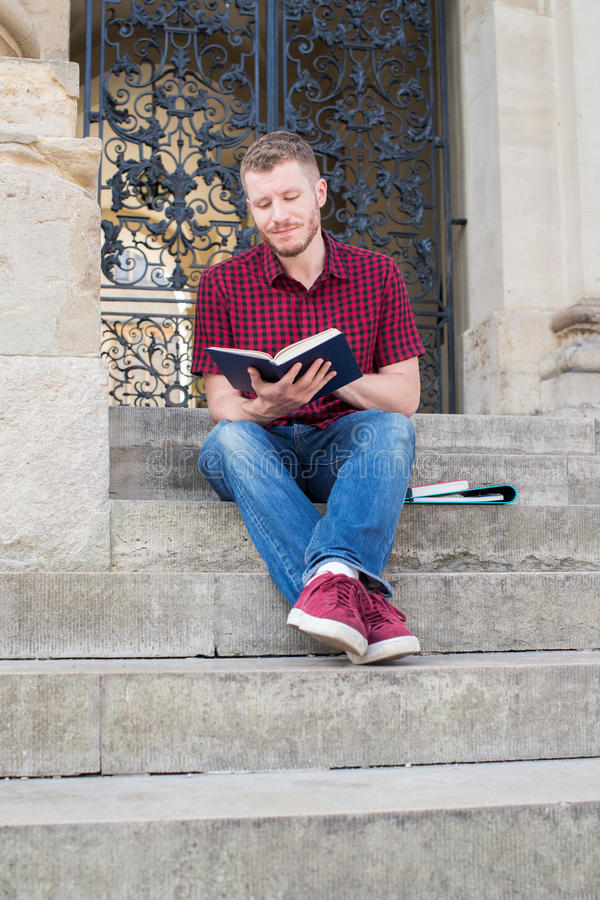 Male University Student Sitting On Steps And Reading Outside Building royalty free stock image