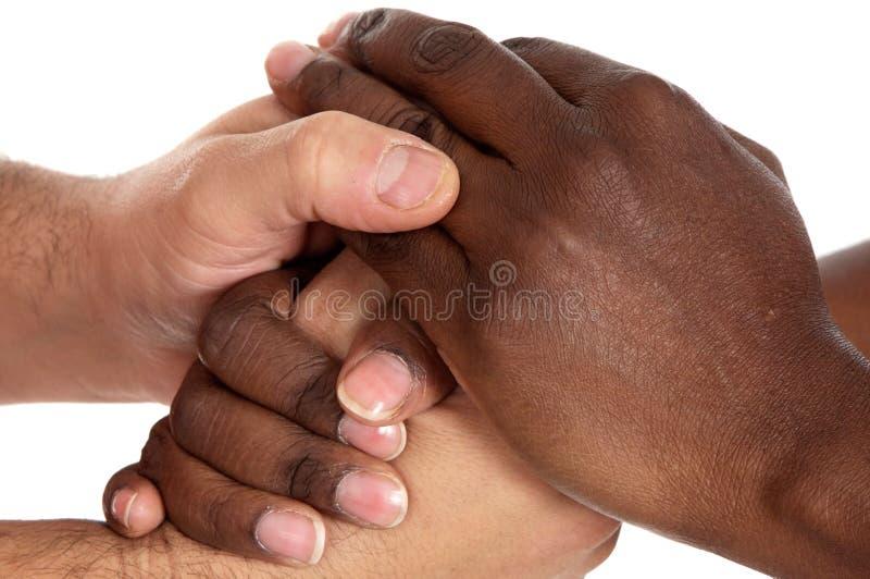 male uppröra för afrikanska caucasian händer arkivbild