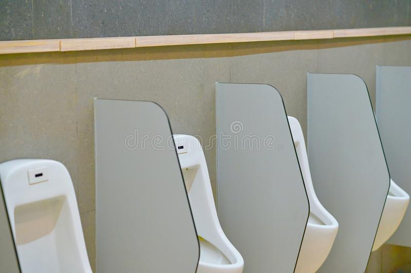 Male urinal with cover in toilet stock image